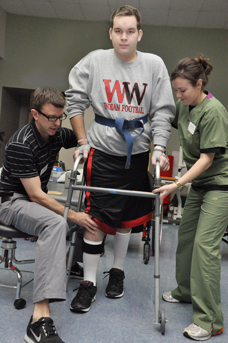 Joel Meisinger stayed focused on his goal to walk after sustaining an incomplete spinal cord injury in a September car accident. Helping Joel refine his steps are Matt Ulmer, PT (left) and Christine Widman, PTA.